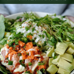 hands holding salmon poke bowl with salad