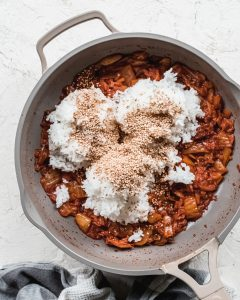 white rice, sesame seeds, and kimchi in non stick pan
