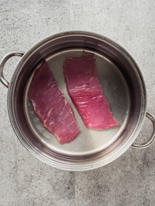 flank beef steak covered with water in pot