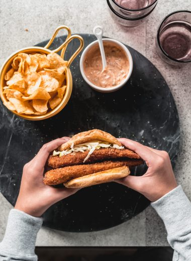 two hands holding fried fish sandwich