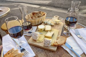 Bread and cheese with red wine in glasses and carafes