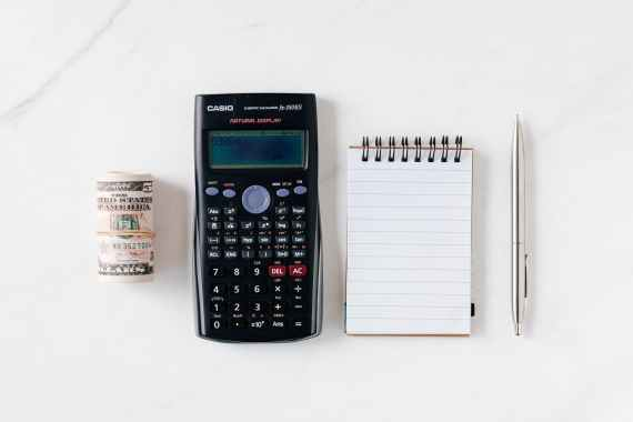composition of calculator with paper money and notebook with pen