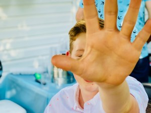 Teen boy- hand in front of camera