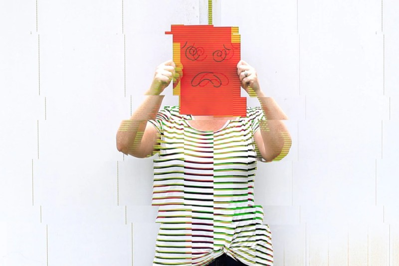 glitching image of a woman holding a paper with an anxious face