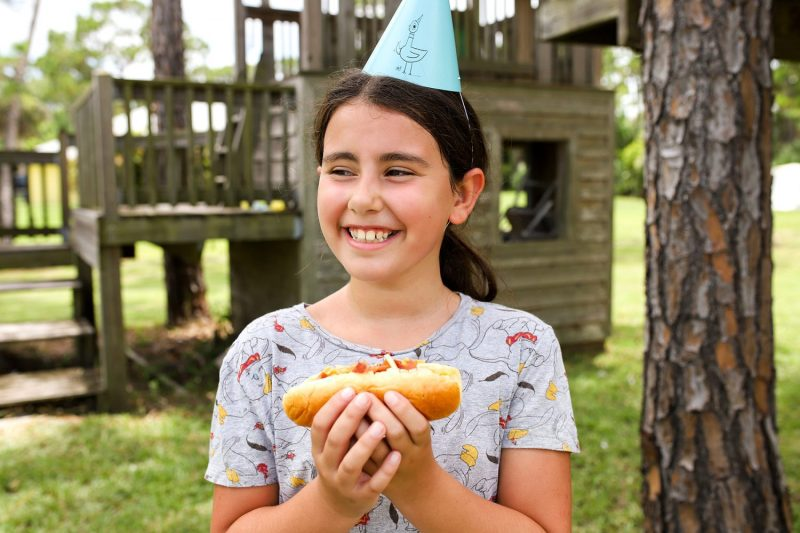 girl smiling and wearing a mo willems pigeon birthday hat and holding a hot dog