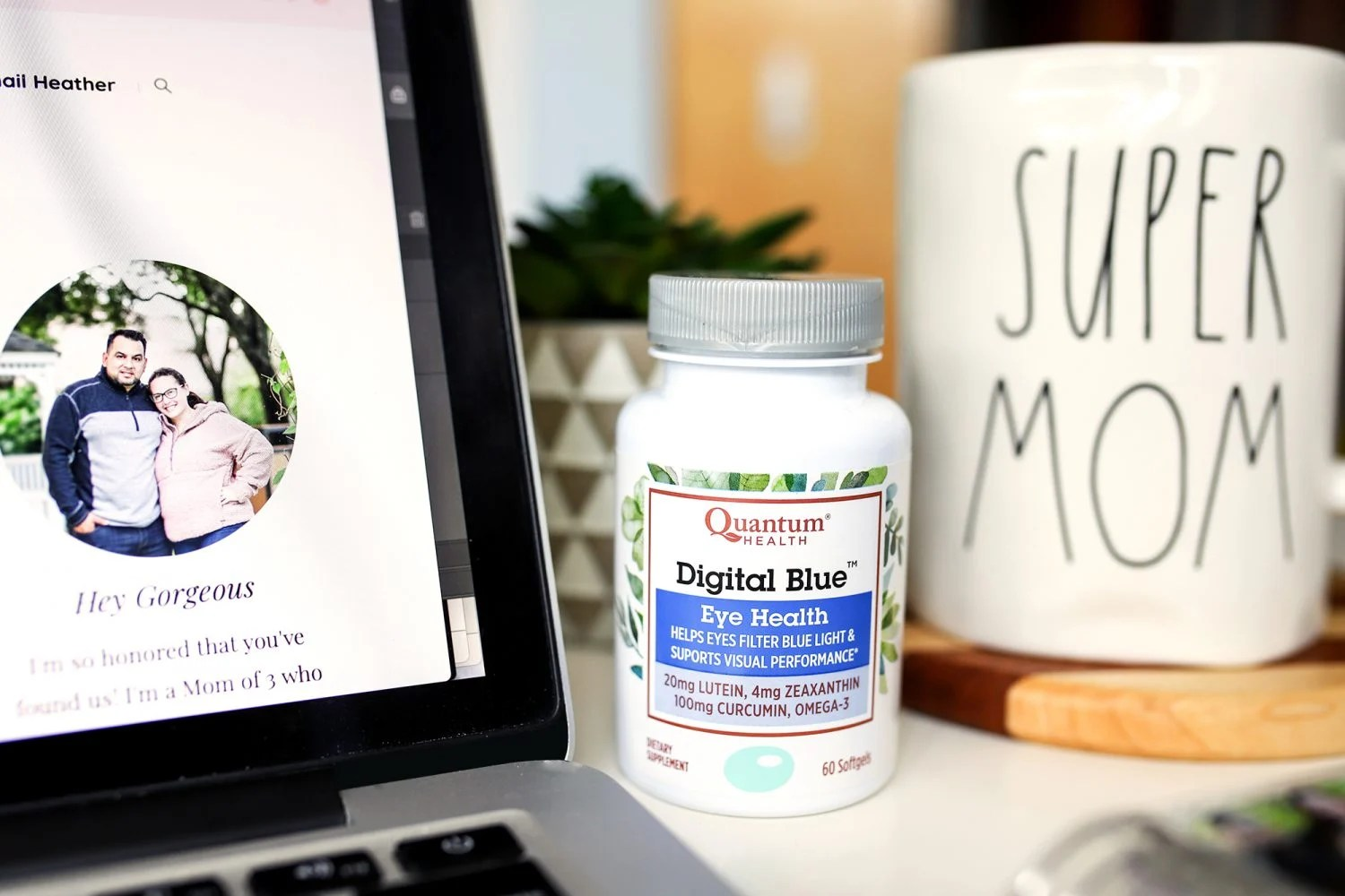 Bloggers desk with laptop, super mom cup and digital blue eye health by quantum health