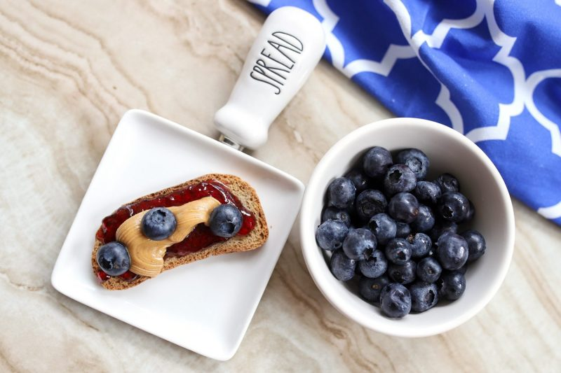 melba toast with peanut butter and jelly and blue berries