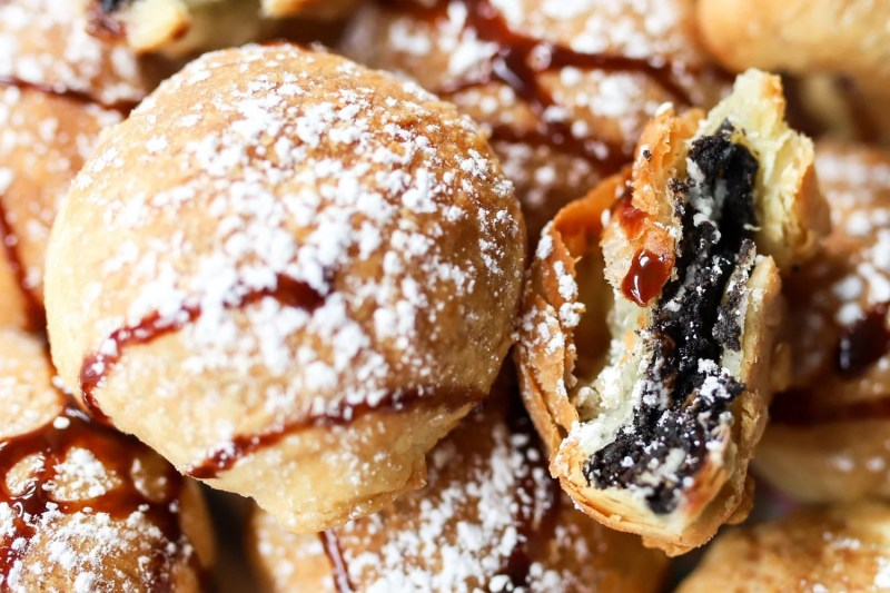 close up of air fried oreos with chocolate drizzle and powdered sugar