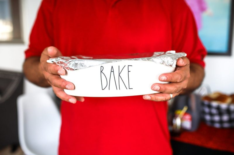 man carrying a bake dish with aluminum foil