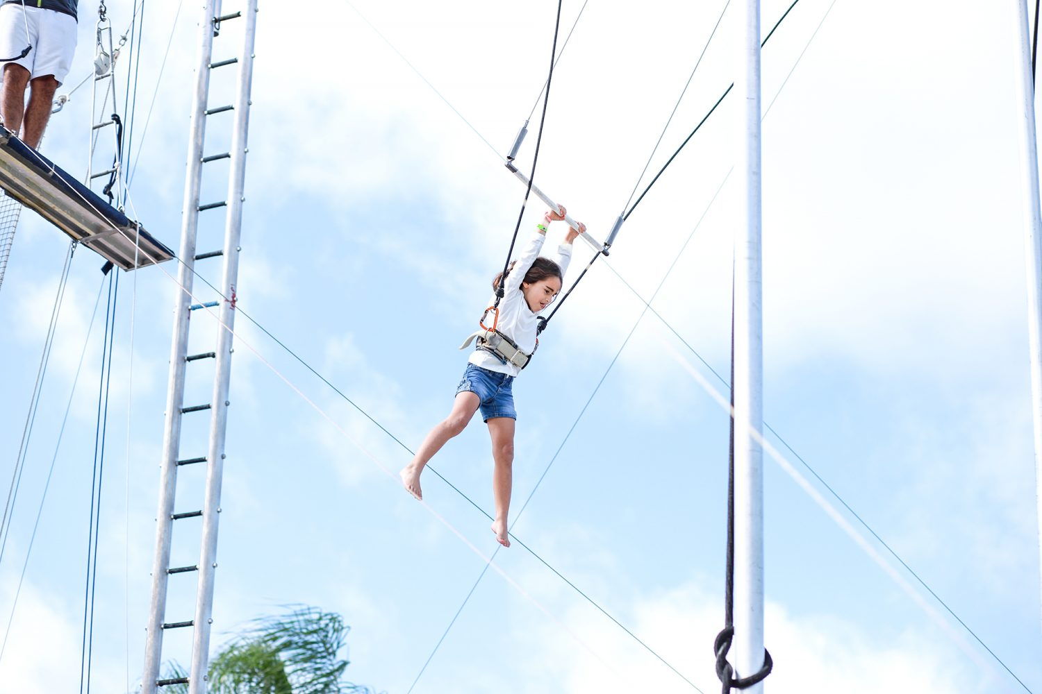 little girl swinging from trapeze