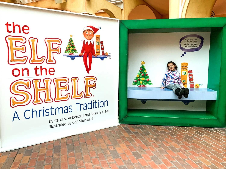 Little girl sitting inside Elf on the Shelf box