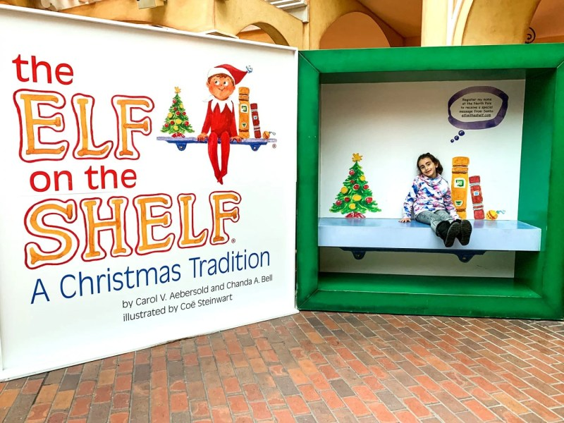 Little girl sitting inside Elf on the Shelf box