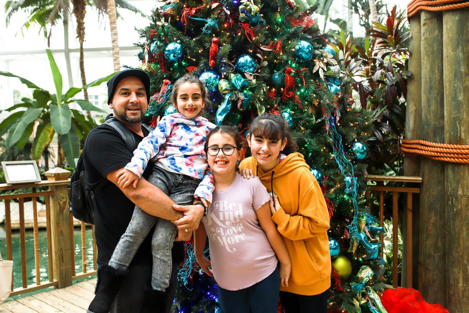 Family standing in front of a christmas tree