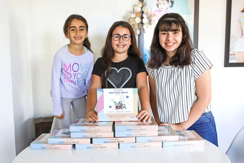 three girls standing behind a pyramid of puzzles