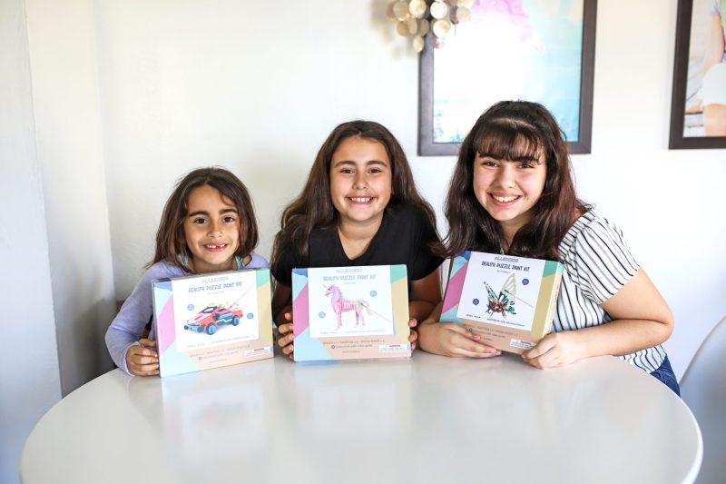 three girls showing their allessimo puzzles