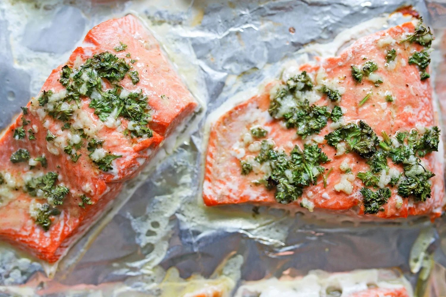cooked salmon fillets on foil lined baking sheet