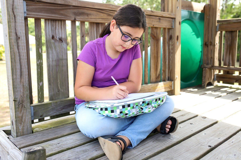 girl writing using a lap desk