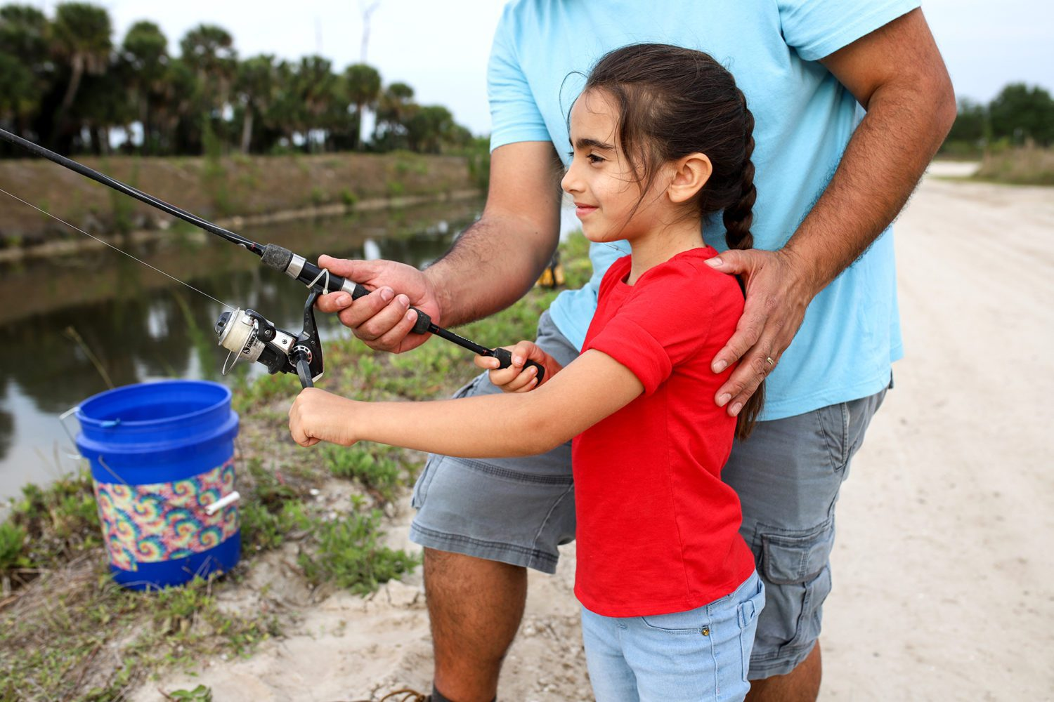 dad teaching daughter how to fish