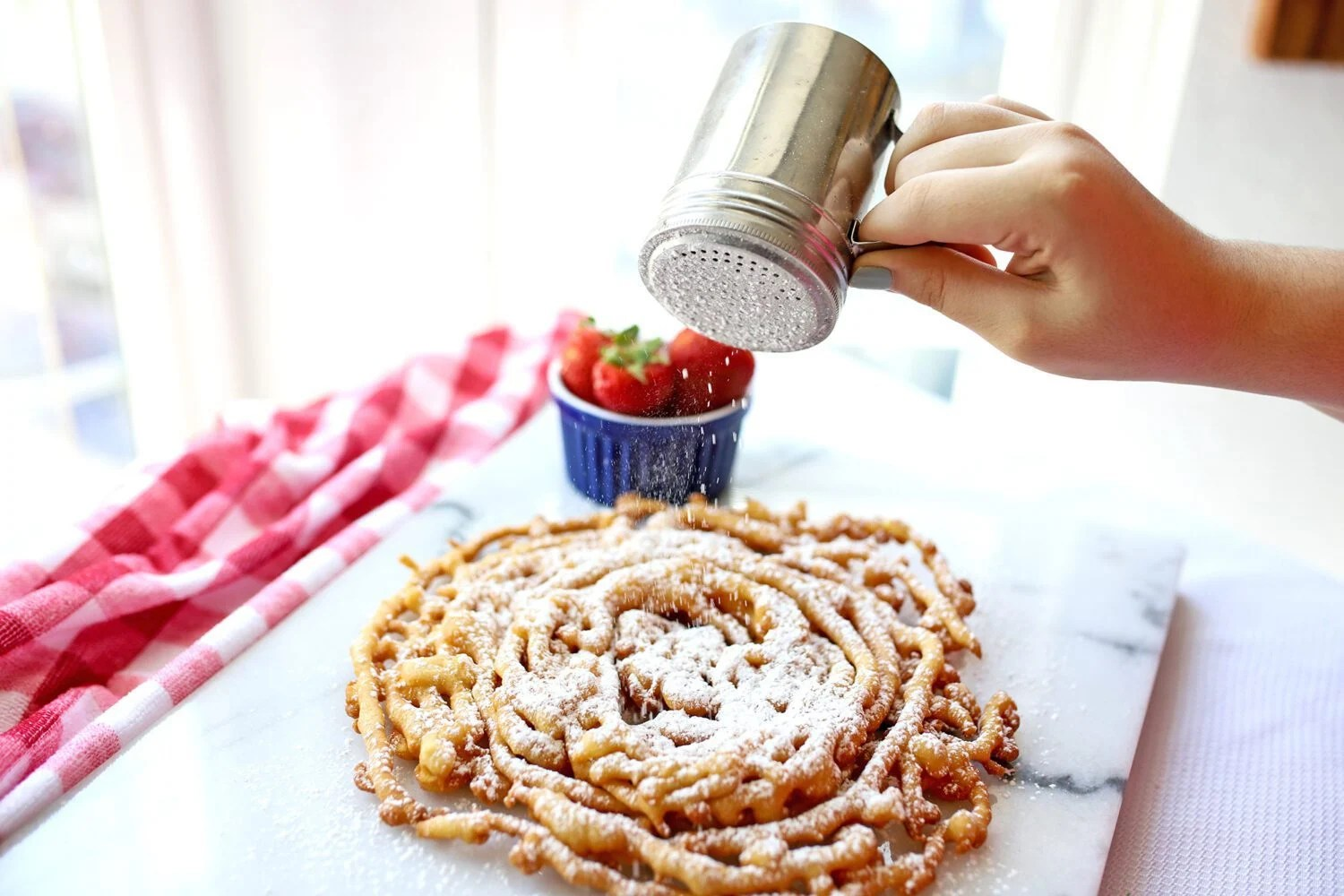 woman adding powdered sugar to fried dough