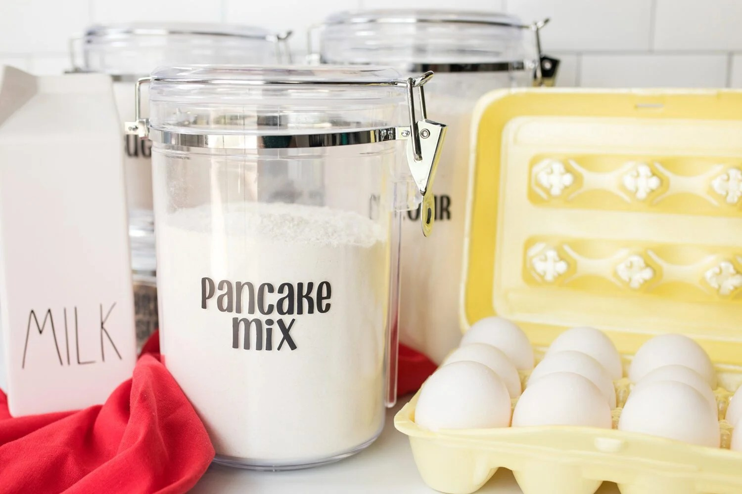 pancake mix in a container next to eggs