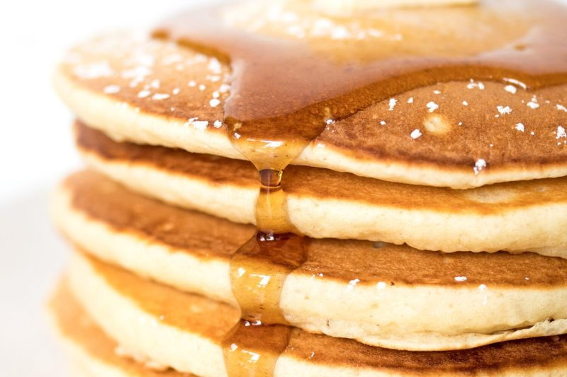 close up of a stack of pancakes with maple syrup