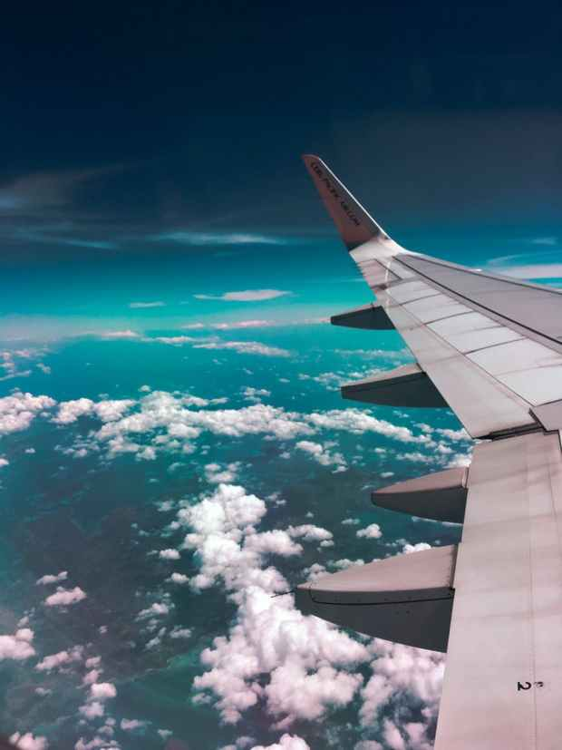 airplane wing towards clouds