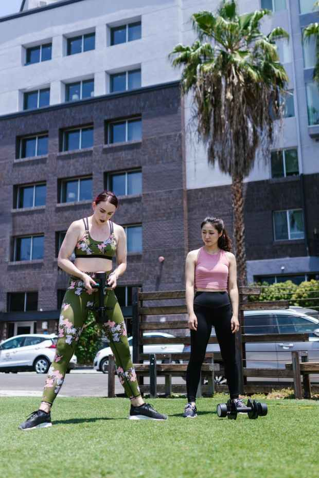 two women in activewear exercising at the park