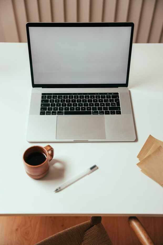 high angle shot of a macbook and cup of coffee on white table