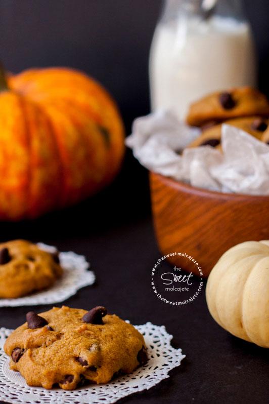 Acercamiento a una Galleta de Calabaza con Chispas de Chocolate. Al fondo se ve el plato lleno de galletas, un vaso de leche y calabazas decorativas.