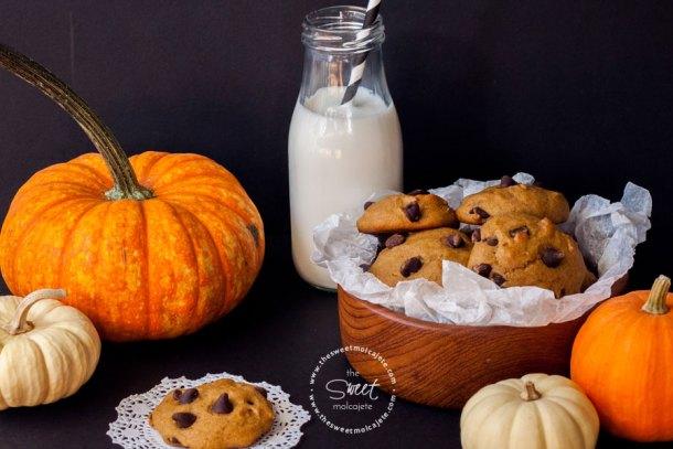 Galletas de Calabaza con Chispas de Chocolate dentro de un plato de madera hondo, hay calabacitas decorativas y un frasco de leche con popote al fondo