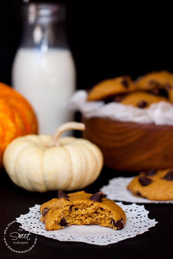 Al frente se ve una galleta mordida sobre un dollie de papel, al fondo se alcanza a ver un vaso de leche y un plato de madera lleno de Galletas de Calabaza con Chispas de Chocolate