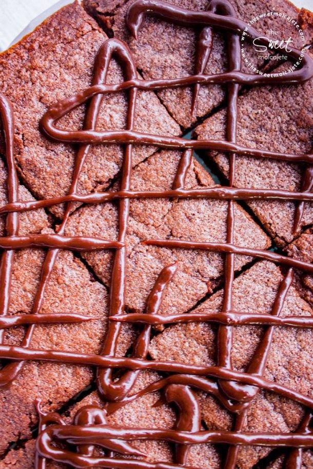 Vista de arriba de varios cuadritos de brownies cubiertos con líneas de ganache de chocolate