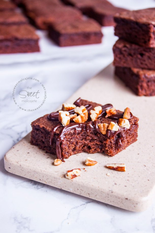 Vista de frente de un brownie con un poco de ganache de chocolate encima y nueces mordido