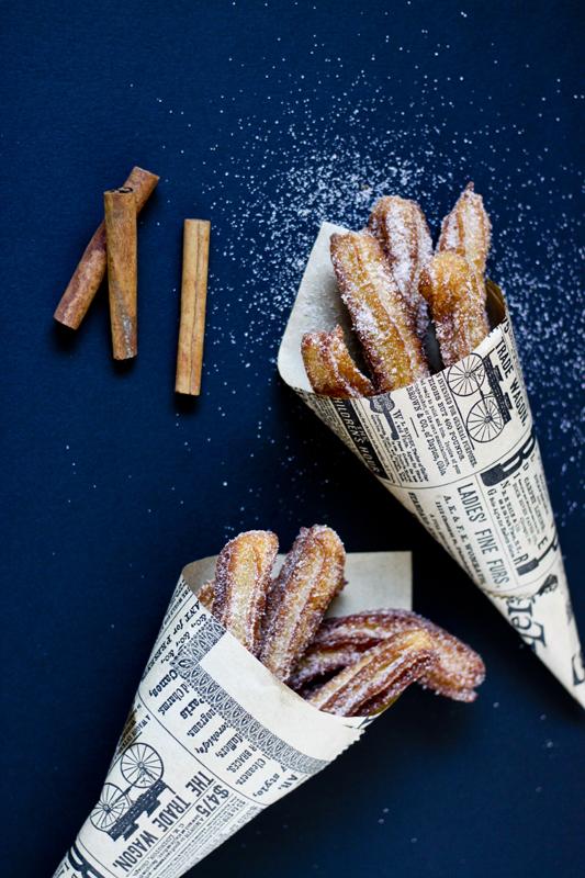 Vista de arriba a dos cucuruchos de papel vintage llenos de churros crujientes y dorados