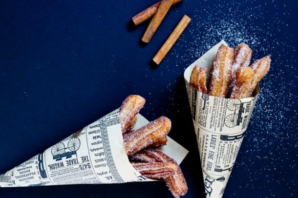 Vista de arriba a dos cucuruchos de papel llenos de churros mexicanos doraditos y crujientes, espolvoreados con azúcar