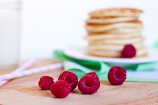 Acercamiento a varias frambuesas frescas, se ve un altero de hotcakes en un plato a lo lejos