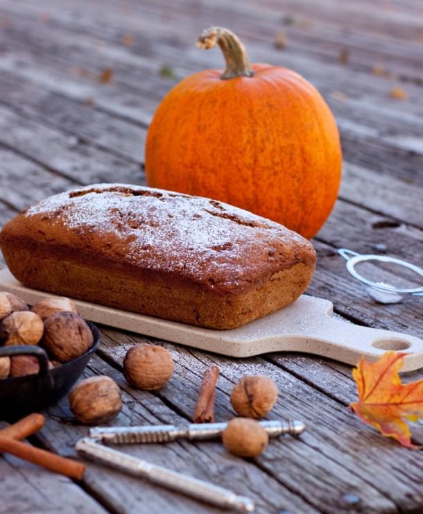 Imagen de un Pan de Calabacín y Calabaza con azúcar glass arriba, hay una calabaza grande al fondo y nueces sobre la mesa rústica de madera