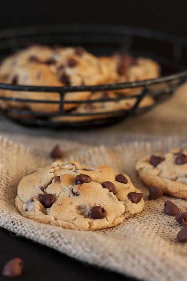 Acercamiento a una galleta de chispas de chocolate, al fondo un plato lleno de galletas