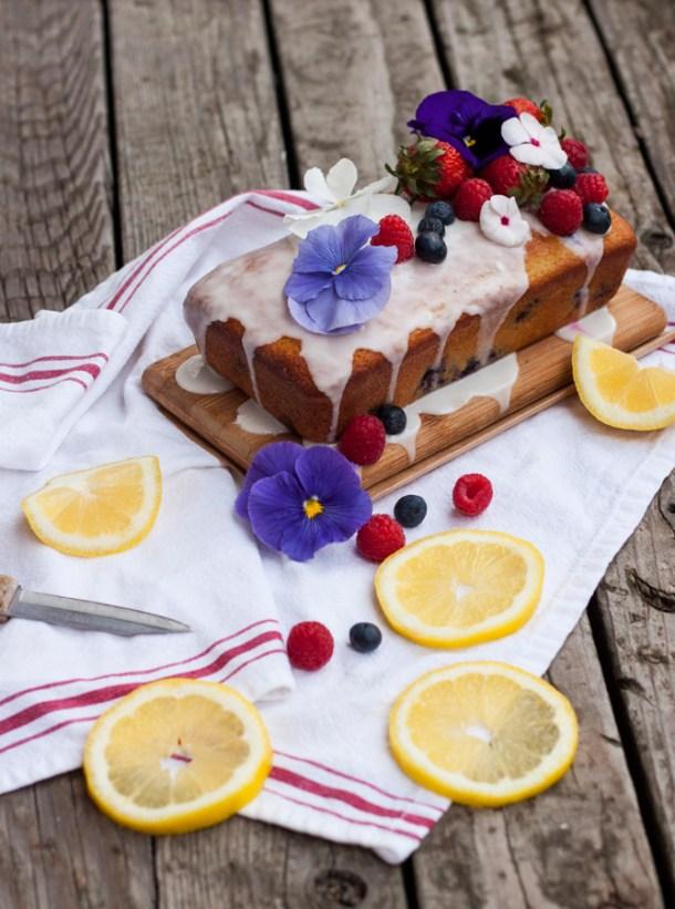 Panqué glaseado sobre una tablita con rodajas de limón y otras frutas frescas en la mesa