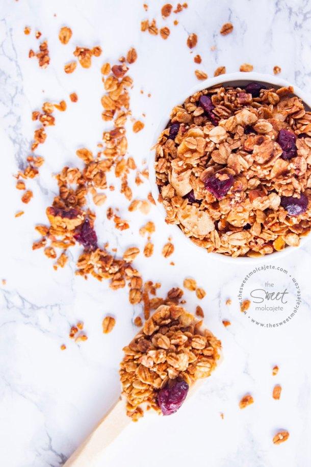 Vista de arriba a un recipiente lleno de granola casera con una ccuchara de madera a lado y granola alrededor