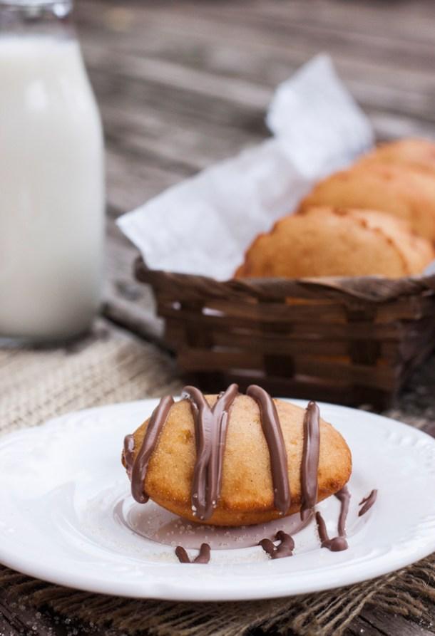Fotografía de una Gordita Dulce de Maíz en un plato pequeño, la gordita tiene chocolate derretido encima. Al fondo se ve un frasco con leche y un canasto con más gorditas dulces