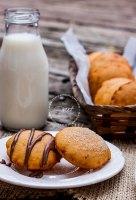 Dos gordtitas dulces de maíz infladas, una con chocolate y la otra con azúcar, al fondo más gorditas y un bote de cristal de leche