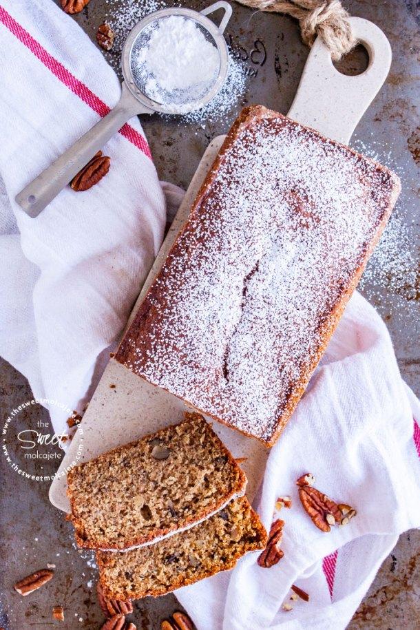 Vista de arriba a un pan de platano espolvoreado con azucar glass con algunas rebanadas cortadas