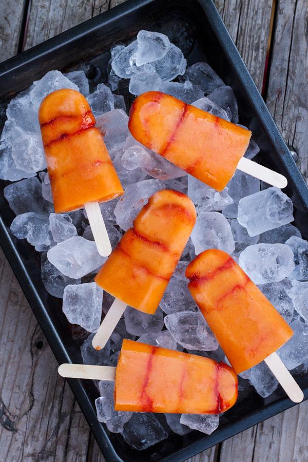 Paletas heladas de mango con chile sobre una charola llena de hielos