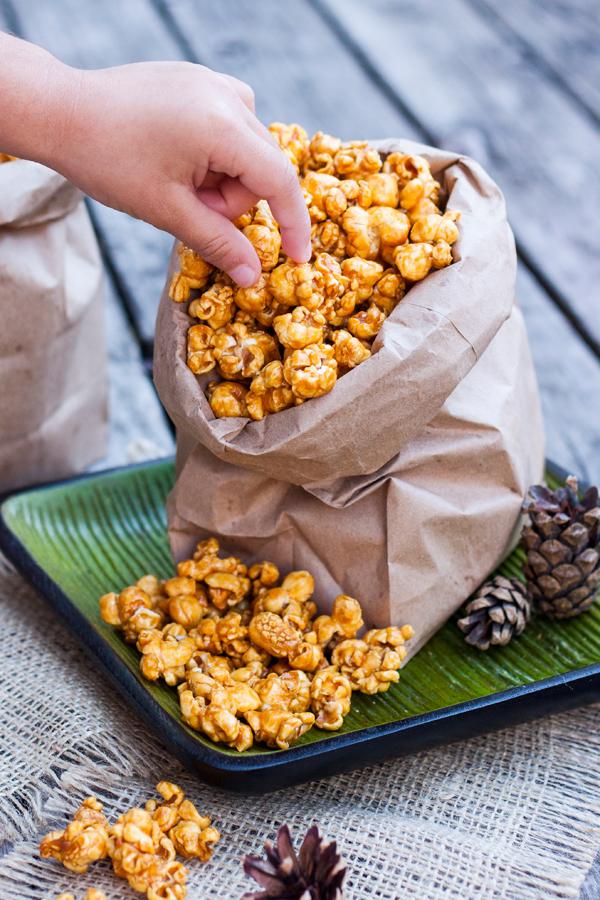 Manita agarrando Palomitas de una bolsa con palomitas de caramelo
