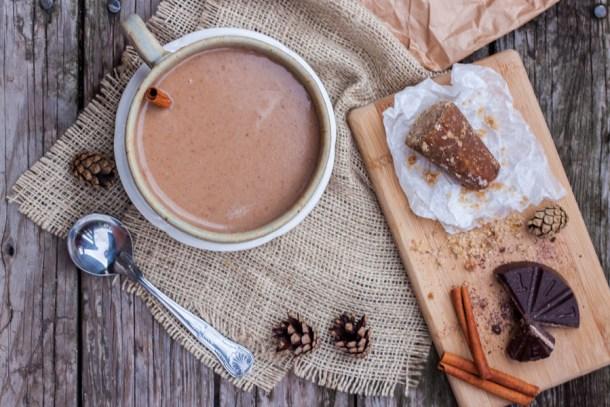 Vista de arriba a una mesa con una taza de champurrado y una tablita con piloncillo, canela y chocolate mexicano