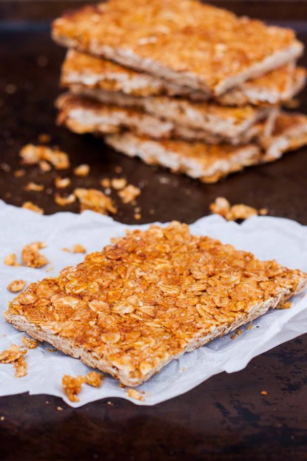 Acercamiento a una barra de avena y miel, hay varias barritas de granola al fondo