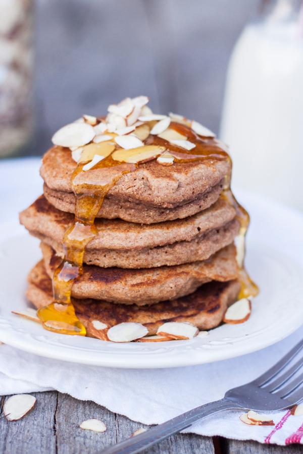 Hotcakes integrales servidos con miel y almendras fileteadas