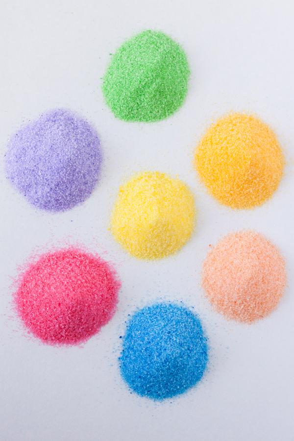 Vista de arriba a 7 montoncitos de azúcar de diferentes colores sobre una mesa blanca