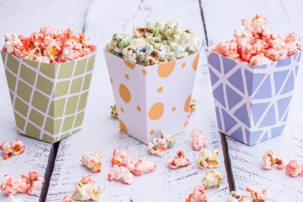 Tres cajitas de carton con patrones llamativos llenas de palomitas dulces de colores rosa y verde